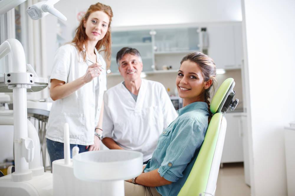 3 Zahnärzte lächeln in einer Zahnarztpraxis.