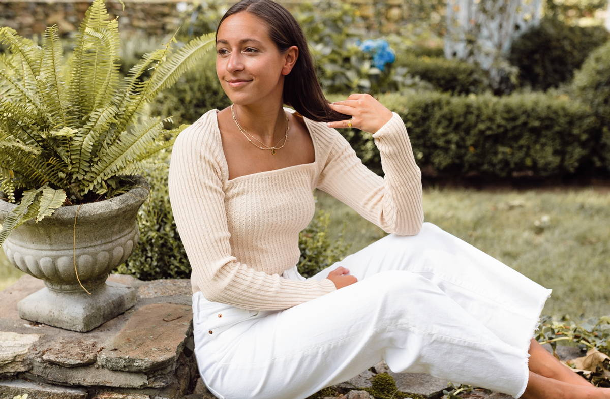 Cait Khosla, founder of Botany Box, lounges outside amongst plants in a white top and white jeans