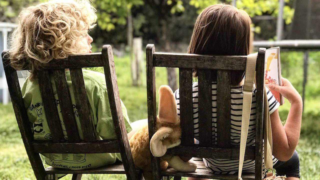 To børn, som sidder og læser i en bog