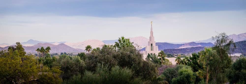 Panoramic Phoenix Temple photo among desert trees and purple hills.
