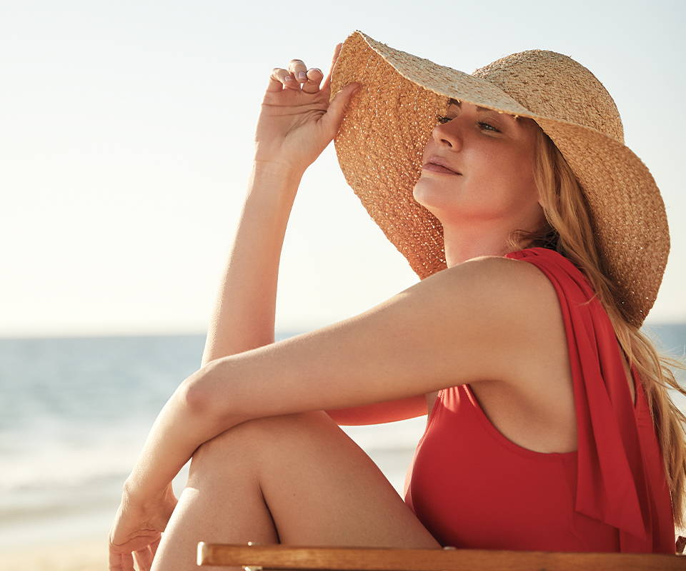 woman sitting in a chair on the beach wearing a floppy sunhat