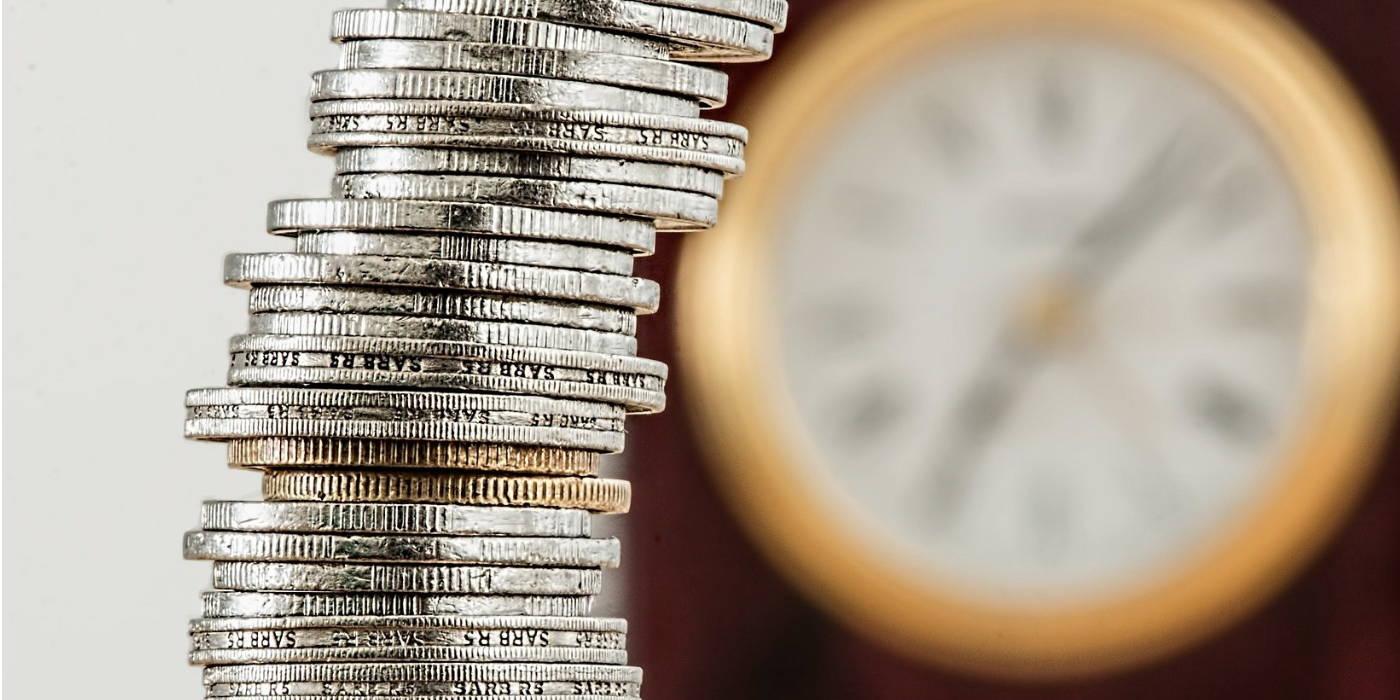 En stak mønter står foran et ur der symboliserer forholdet mellem løbetid og indtjening