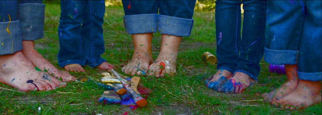 Family of feet covered in paint.