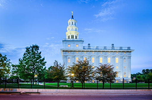Side view of the Nauvoo Temple. It's windows glow against a darkening sky.