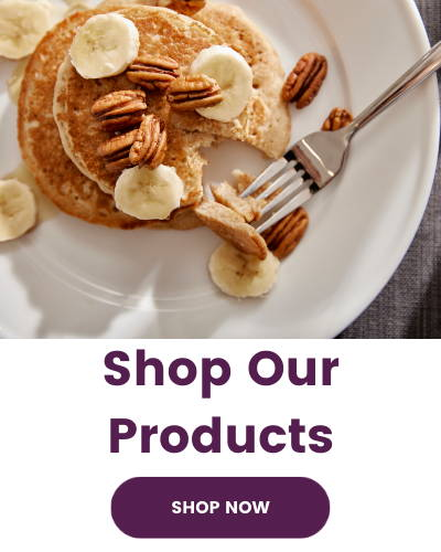 Image shows step one pancakes on a white plate with banana slices and walnuts. Text below image says Shop Our Products with a button that says Shop Now.