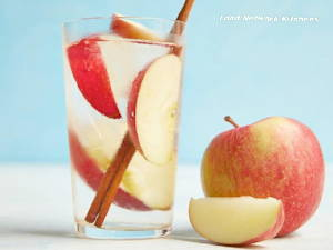 A glass of water with slices of apples and sticks of cinnamon