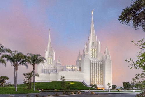 Picture of the San Diego Temple standing against a pink and blu sky.