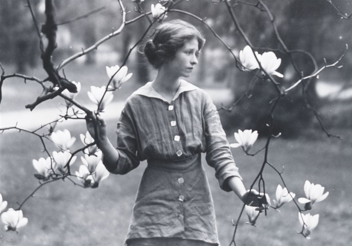 A black and white image of Edna in the outdoors holding a branch from a tree with white flowers.