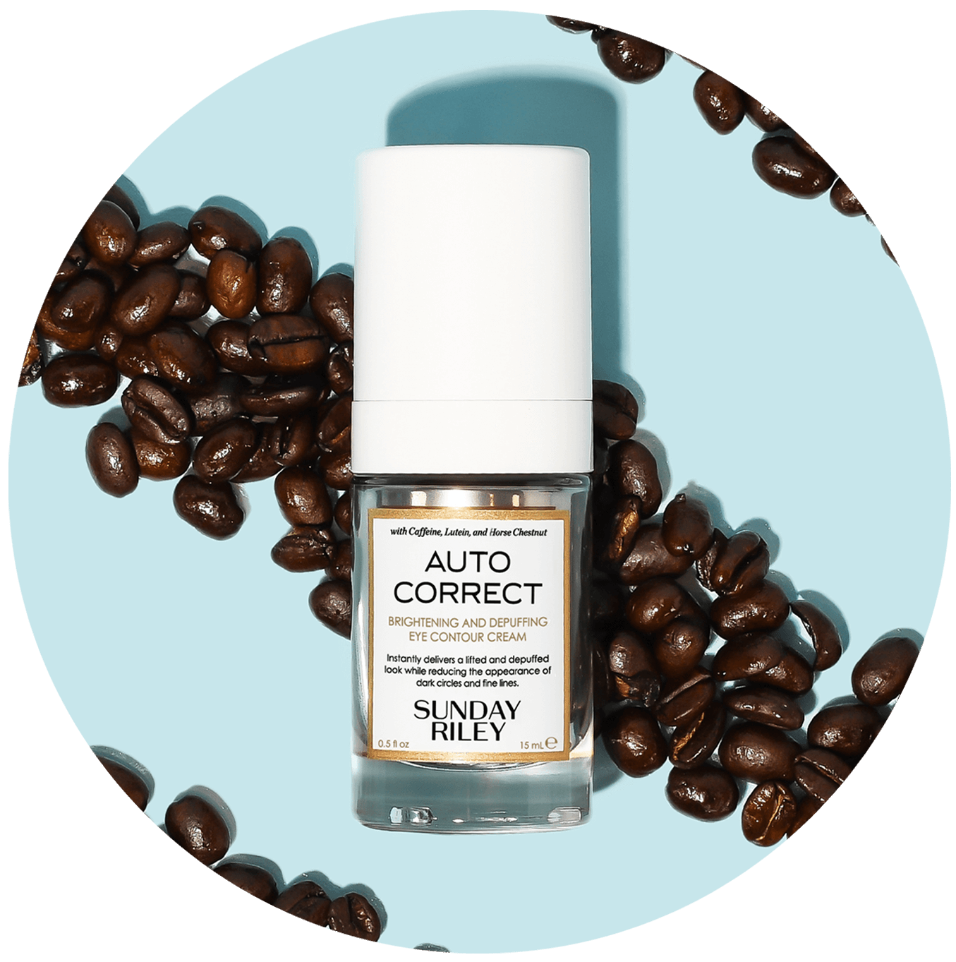 auto correct brightening and depuffing eye contour cream bottle on coffee beans and blue background