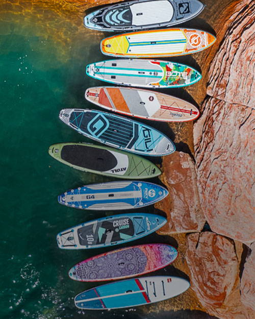 Many paddle boards on the shore