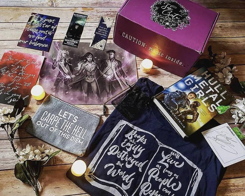 July 2018 Anarchy box theme inclulded Clip On Reading Light, Darkest Minds Zipper Pouch, Red Queen Poster, Fae Crate Exclusive Lux Obsidian Necklace, Cinder Woodmark, Nevernight Print, Shatter Me Shirt, E-Book Download of The Watcher from @watcherbook with Bookmark, and Hullmetal Girls by Emily Skrutskie.