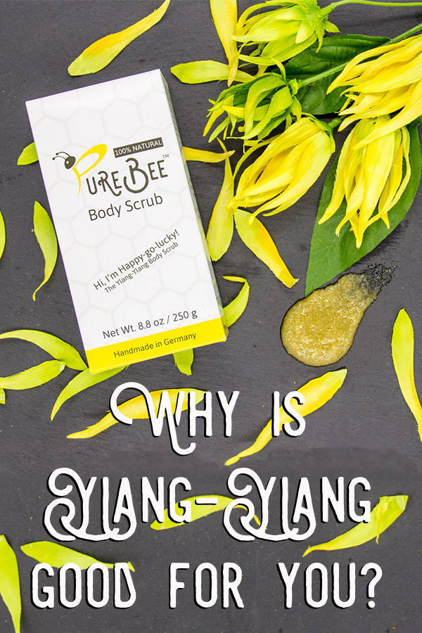 A box of PureBee Body Scrub on a bed of Ylang-Ylang flowers with the headline