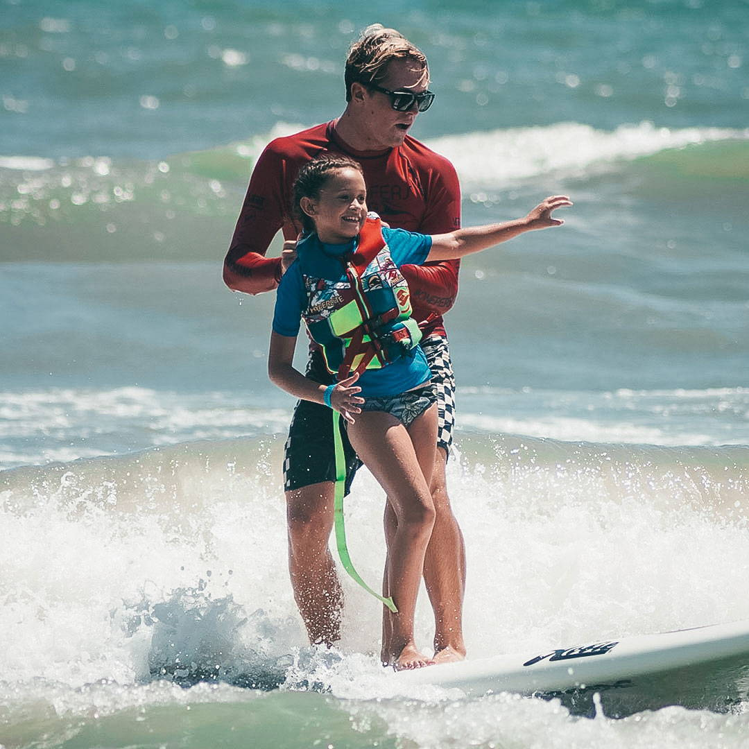 A man wears Rheos sunglasses while surfing alongside his daughter.