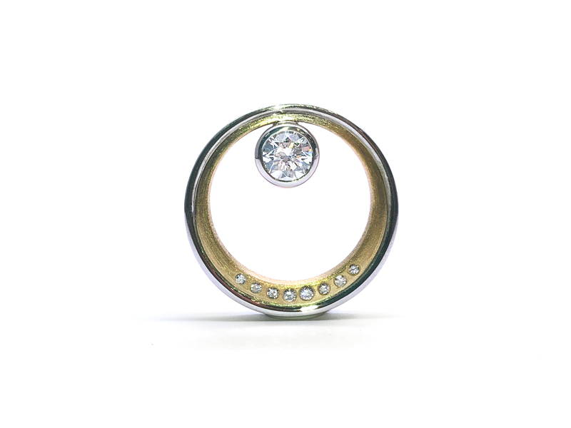 Round pendant in yellow gold with small diamonds on the outline and a large detached insulated diamond in the centre.