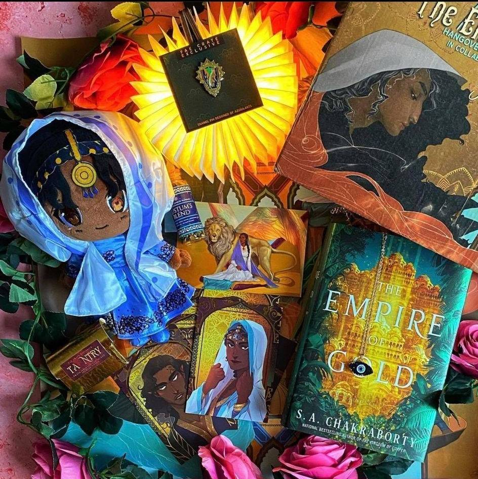 The Empire of Gold by S. A. Chakraborty, Nahri Plushi, Nazar Eye Necklace, Character Card Set, Zulfiqar Enamel Pin, Ta Ntry Incense, Rustam's Blended Tea, Nahid Crest Book LIght, Exclusive Dust Jacket Set, and Foiled Character Cards.