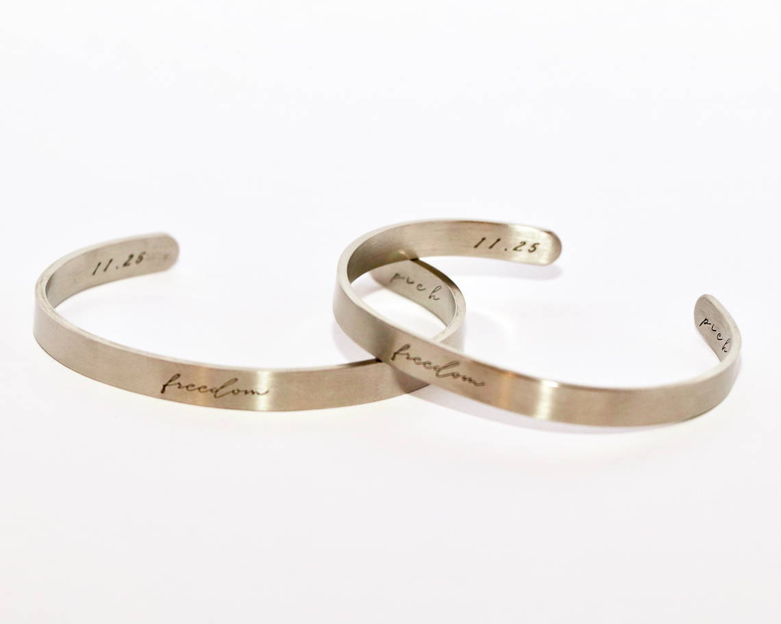 sex trafficking awareness cuff in silver and rose gold on a wooden  table