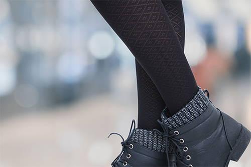 A pair of crossed legs wearing black diamond pattern socks