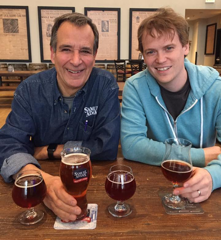 Jim Koch & Joel Gratcyk sitting at a table sharing conversation over Sam Adams beers.