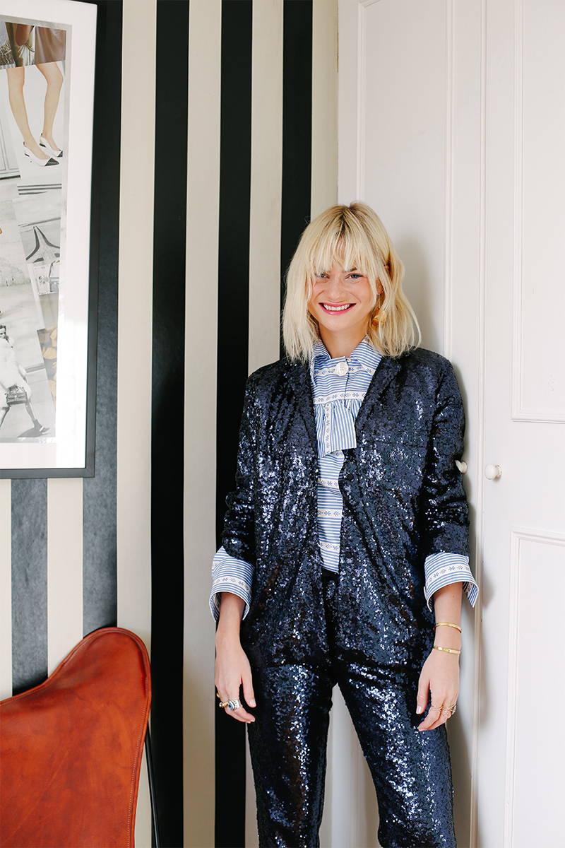 Pandora Sykes poses against a door in YOLKE's Blue Sequin Suit