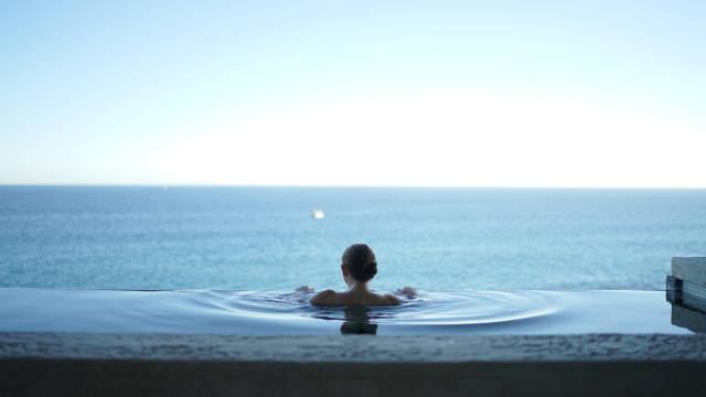 En kvinde, som ligger i en swimmingpool og ser ud over havet