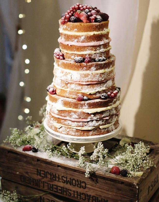 Naked wedding cake with multi-tiers and berries.