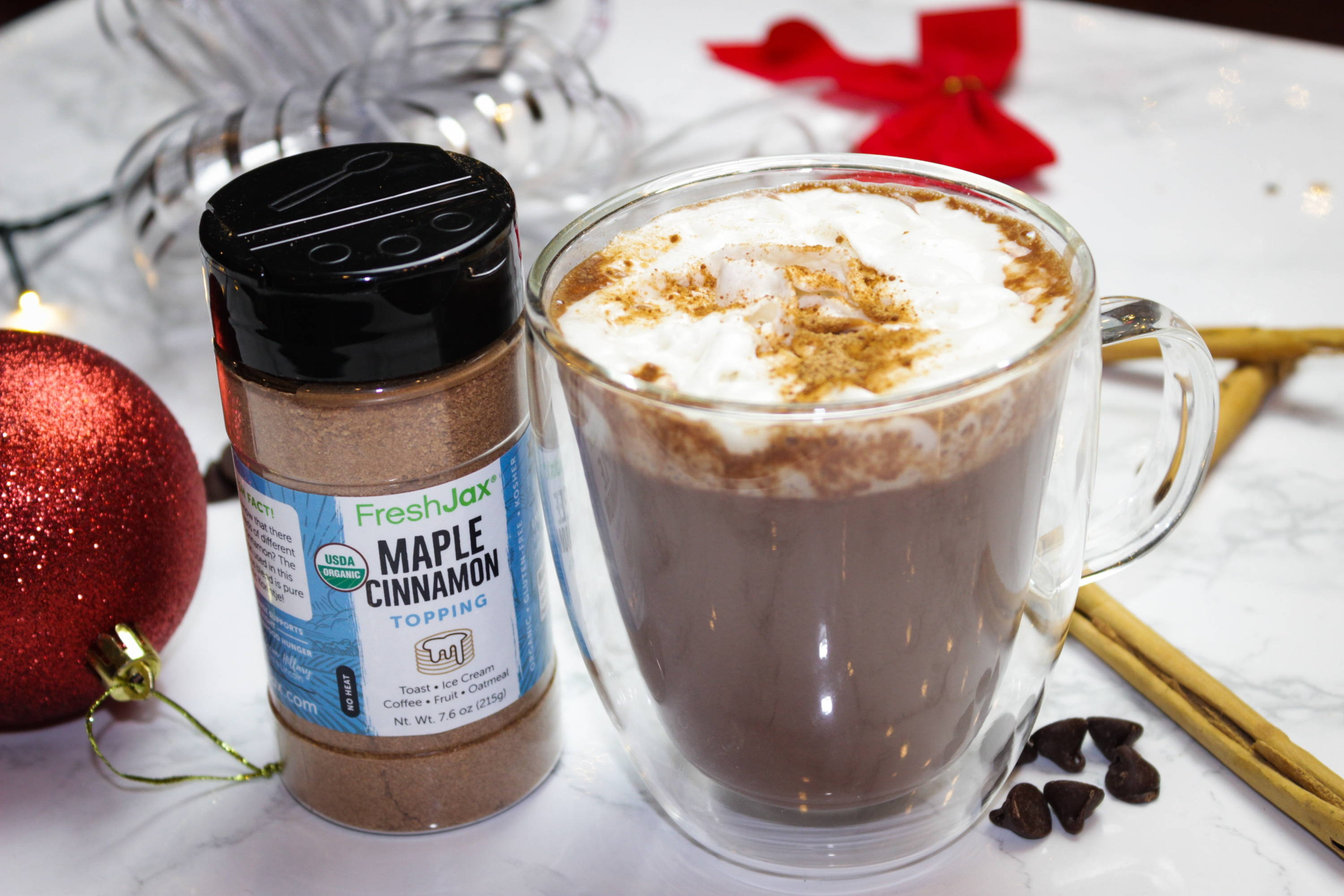 A large bottle of FreshJax Organic Maple Cinnamon Topping next to a mug of vegan hot cocoa topped with whipped cream and maple cinnamon. With a holiday themed background.