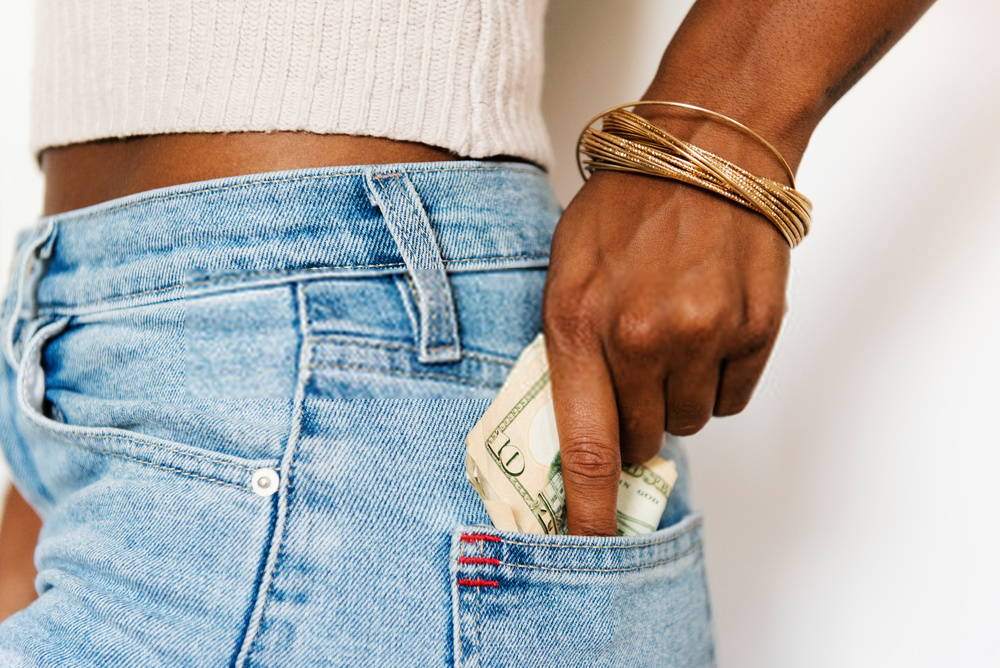 woman putting money in her back jeans pocket