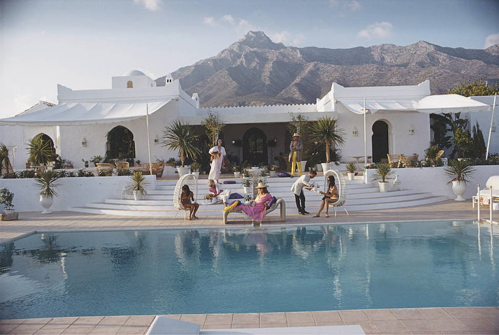 A poolside photograph by Slim Aarons, capturing a white villa with mountains in the distance