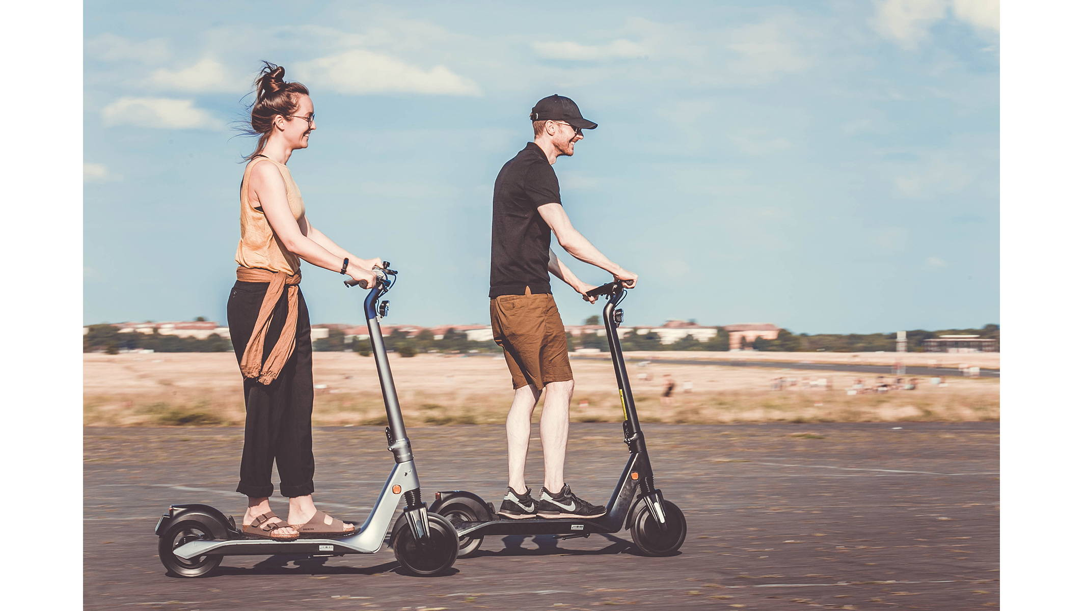 Okai-Electric-Scooter-&-Electric-Bike-Manufacturer-two-friends-riding-and-smiling-on-an-es500-electric-scooter