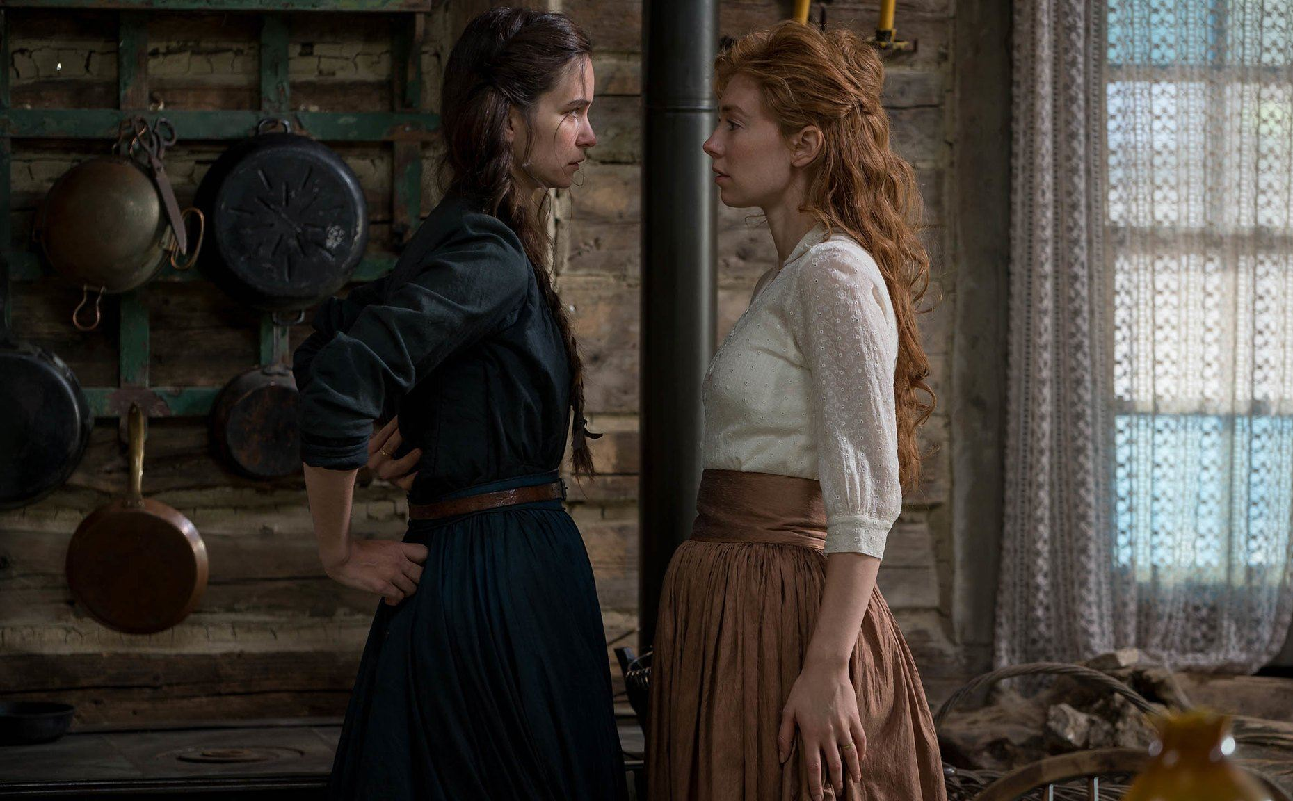 Tallie confronting Abigail inside their cabin. Both have serious looks on their faces.