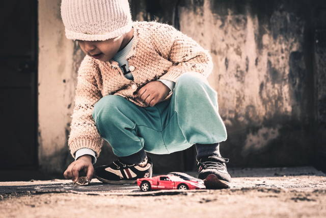 kid playing toy car on the ground