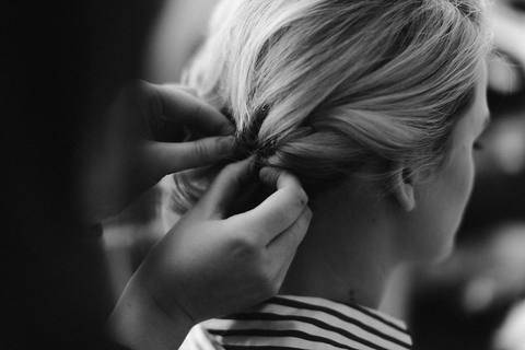 black and white photo of a woman having her hair pinned up
