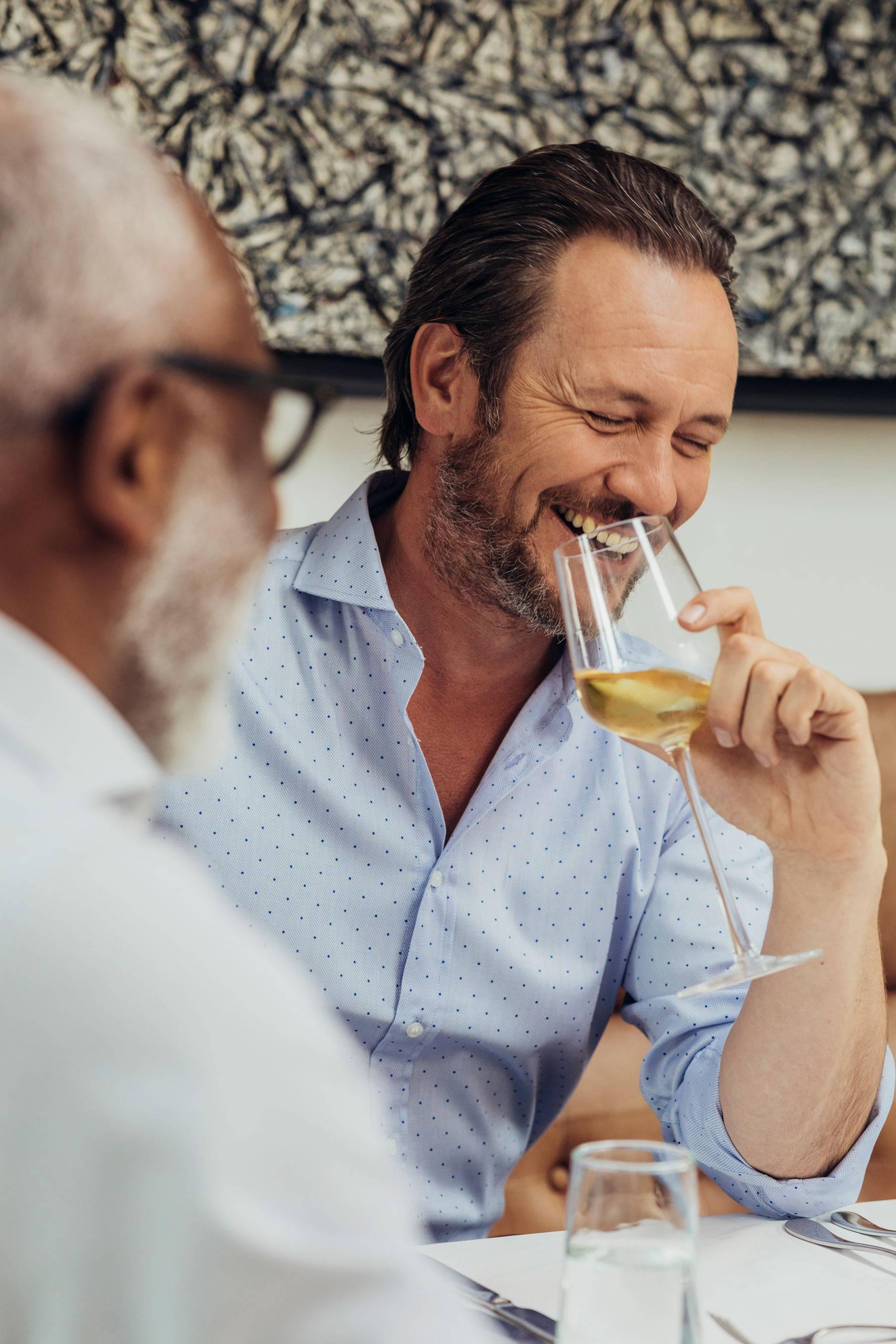 Gentleman drinking wine in blue shirt