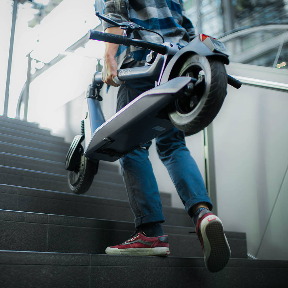 Okai Electric Scooter & Electric Bike Manufacturer, ES500 Electric Scooter Front View Carry Scooter on Stairs