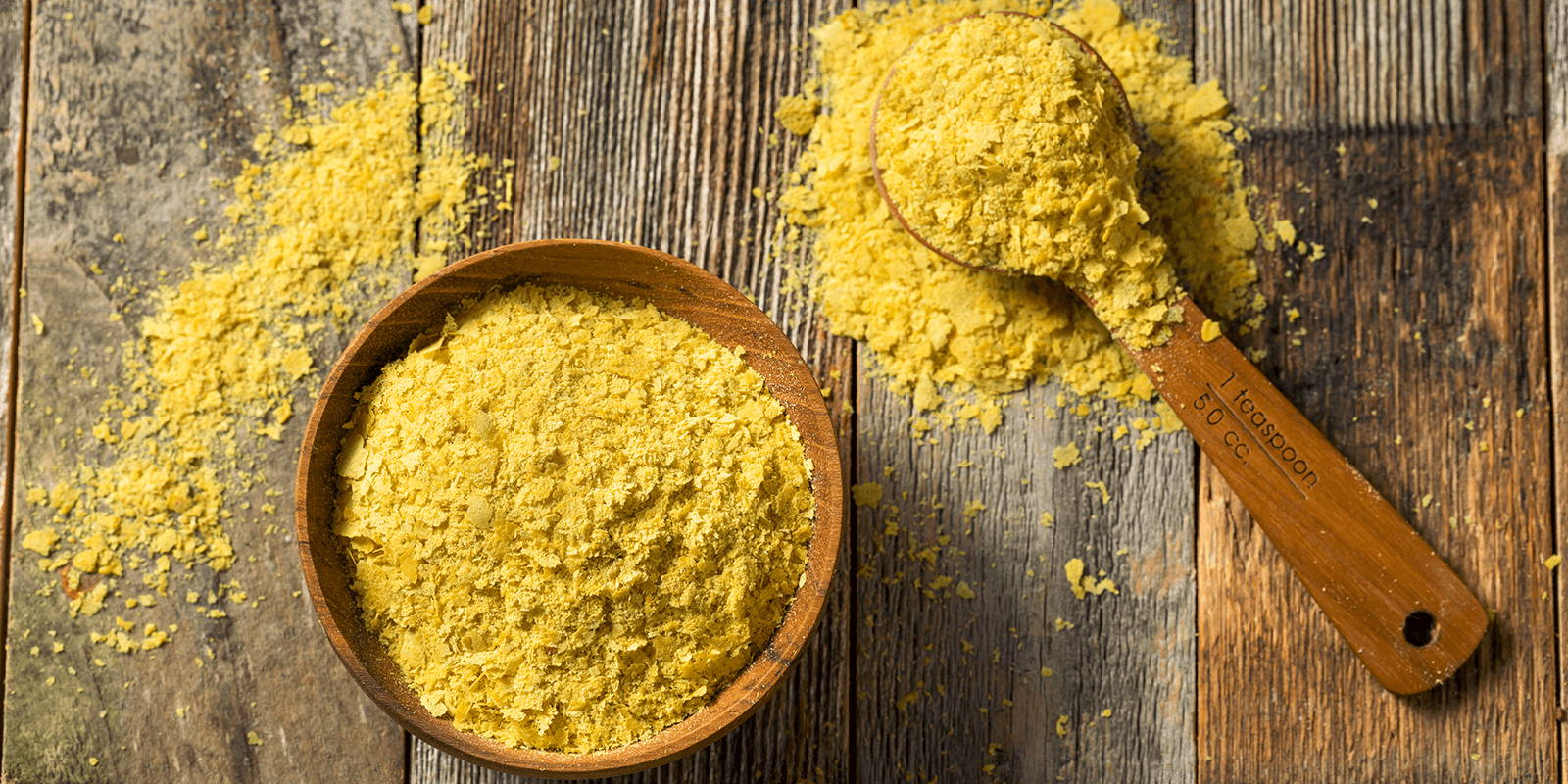 A bowl and spoon of nutritional yeast