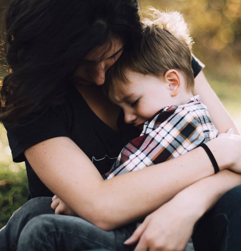 sad child held by mom