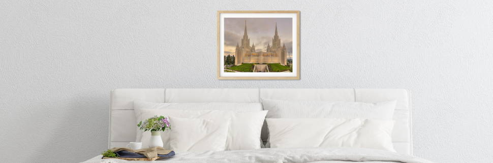 Banner image of a San Diego Temple photo hanging above a white bed.