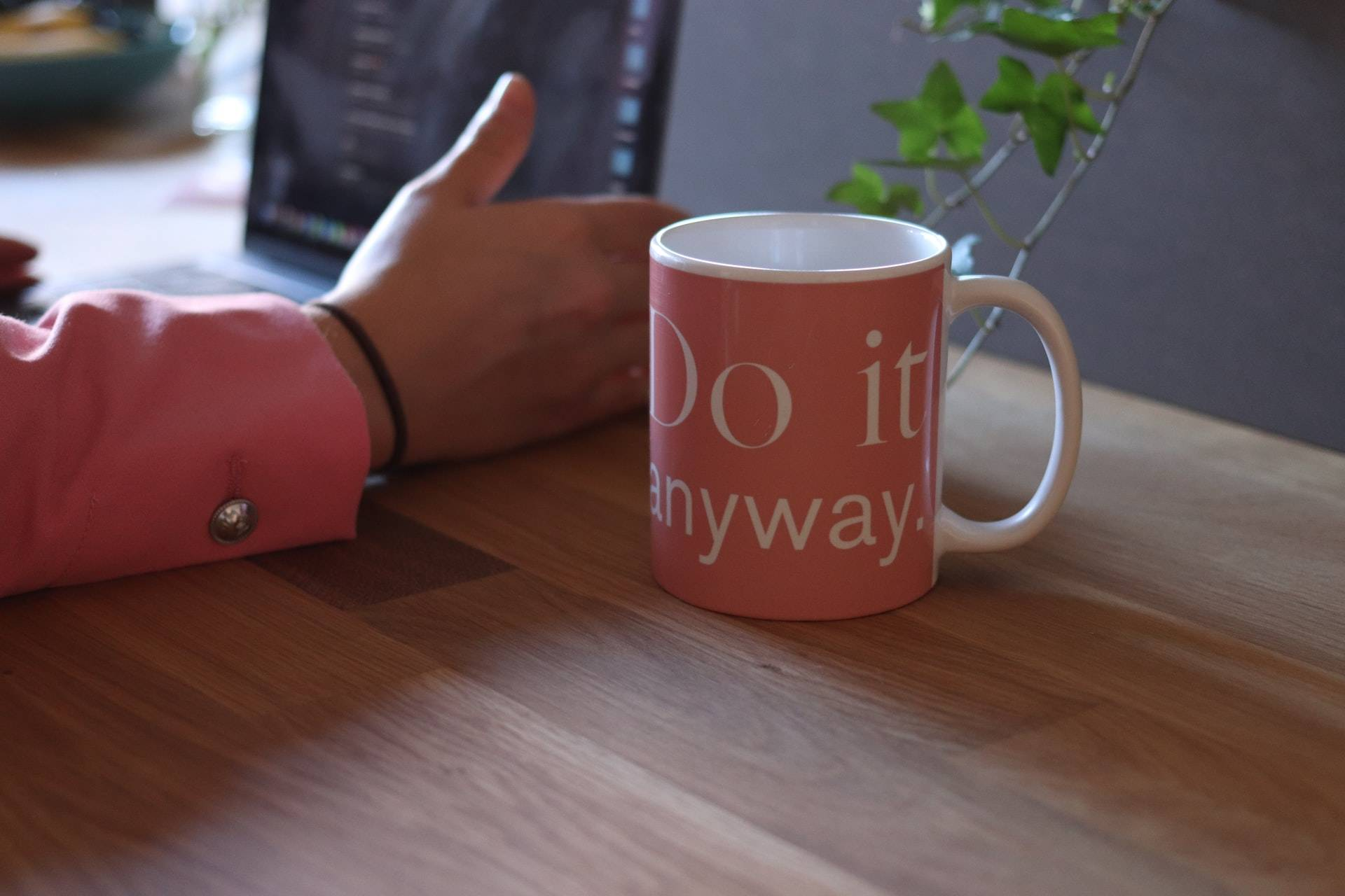 Woman's hand next to a motivational cup