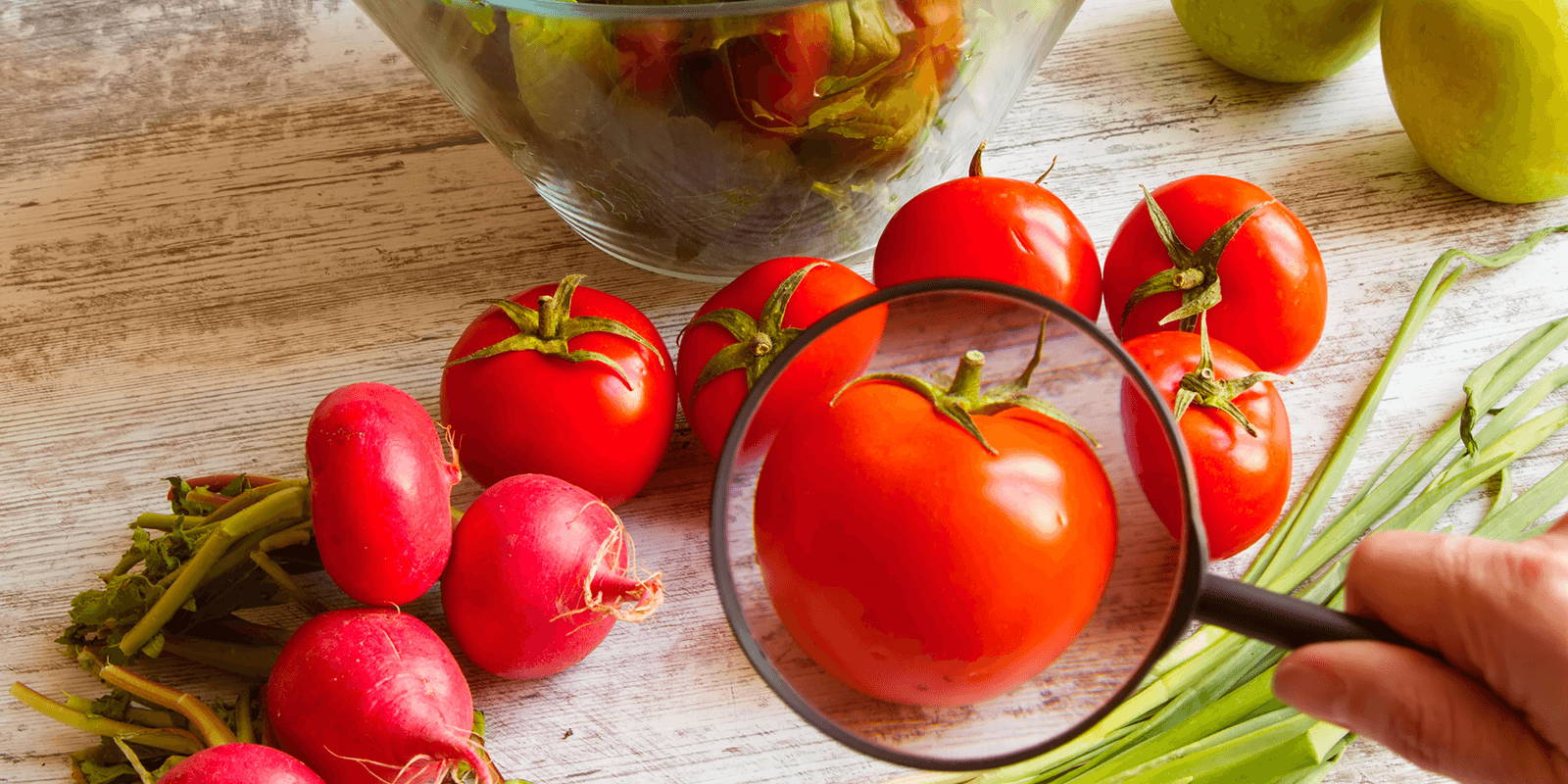 Fresh fruit on counter with a magnifying glass zoomed in on a tomato.