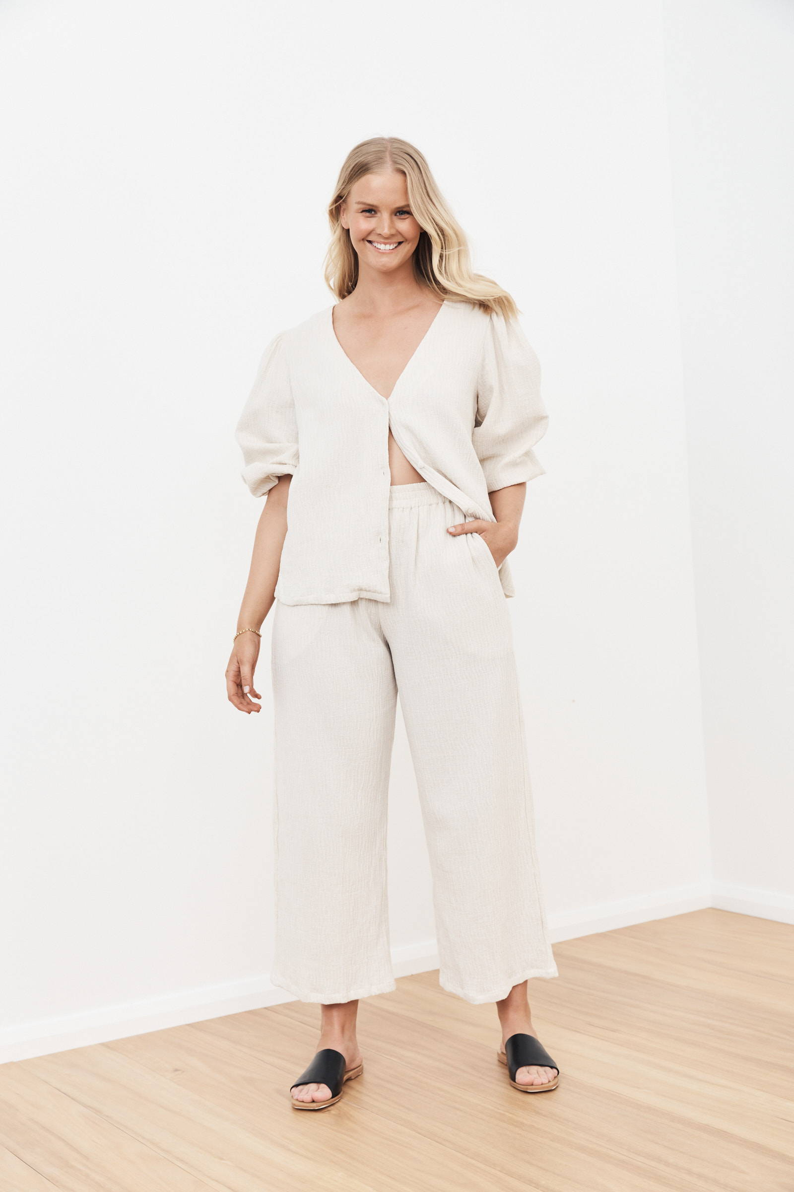 smiling blonde woman wearing natural linen loose clothing with black slides