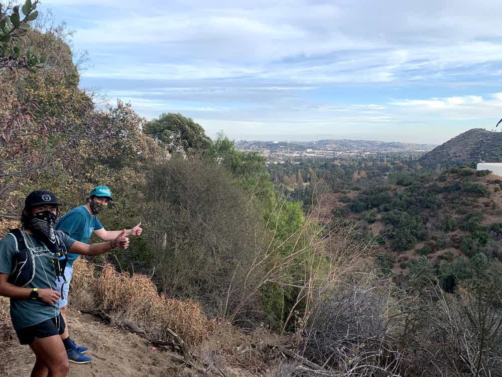 Two hikers giving the thumbs up on a hiking trail to Amir's Garden in Griffith Park Los Angeles