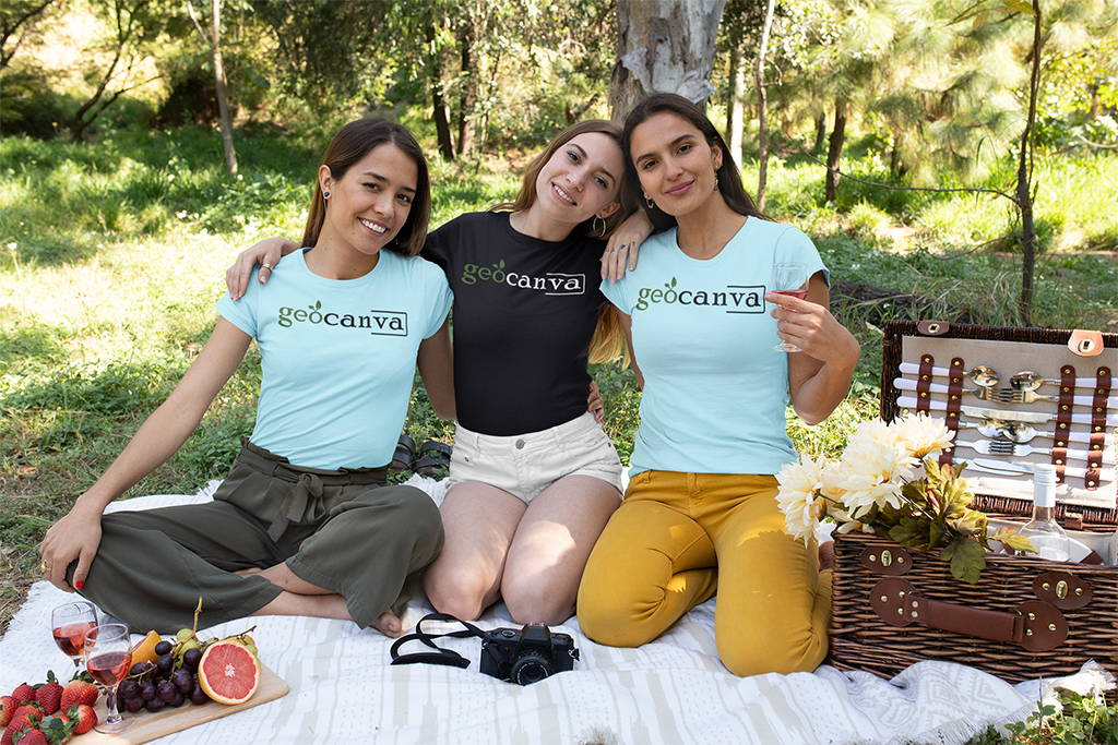 Three women wearing geocanva shirts in a picnic blanket outdoors