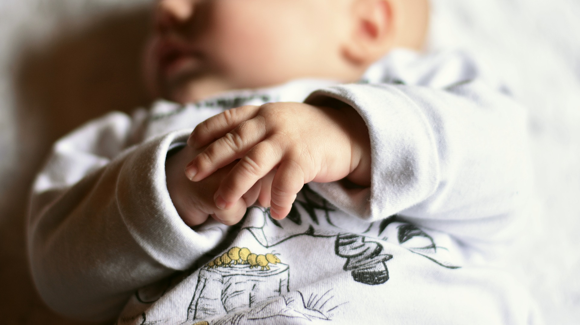 photo of a newborn baby and their hands