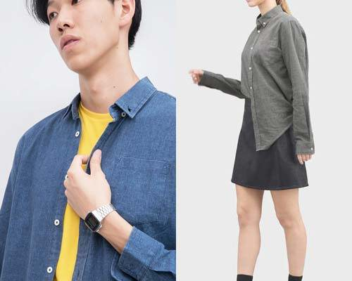 Man wearing sustainable indigo blue button down shirt with yellow t-shirt and silver casio watch and woman wearing charcoal grey Cosmos Studio cotton button up shirt untucked on one side from a black skirt