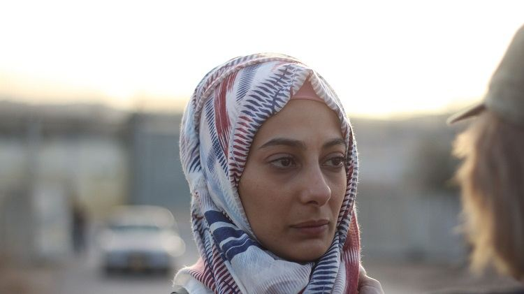 A woman in a head scarf looks to the right.