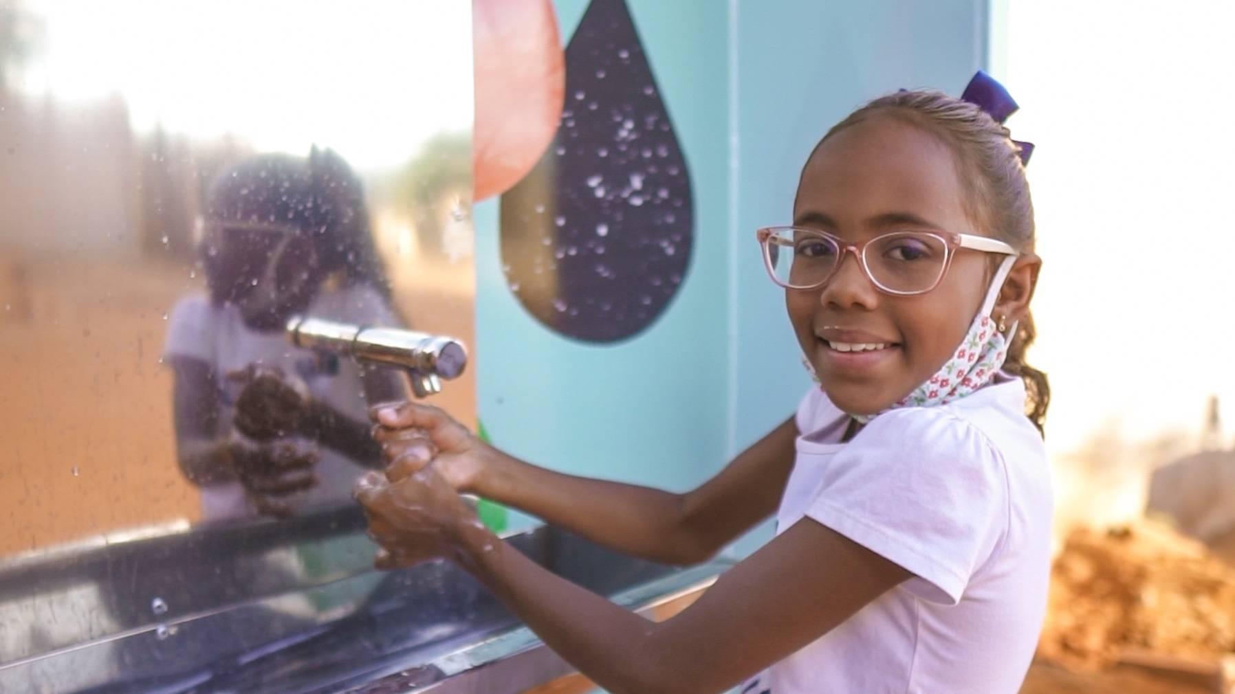 Niña con una de nuestras estaciones de agua en Brasil