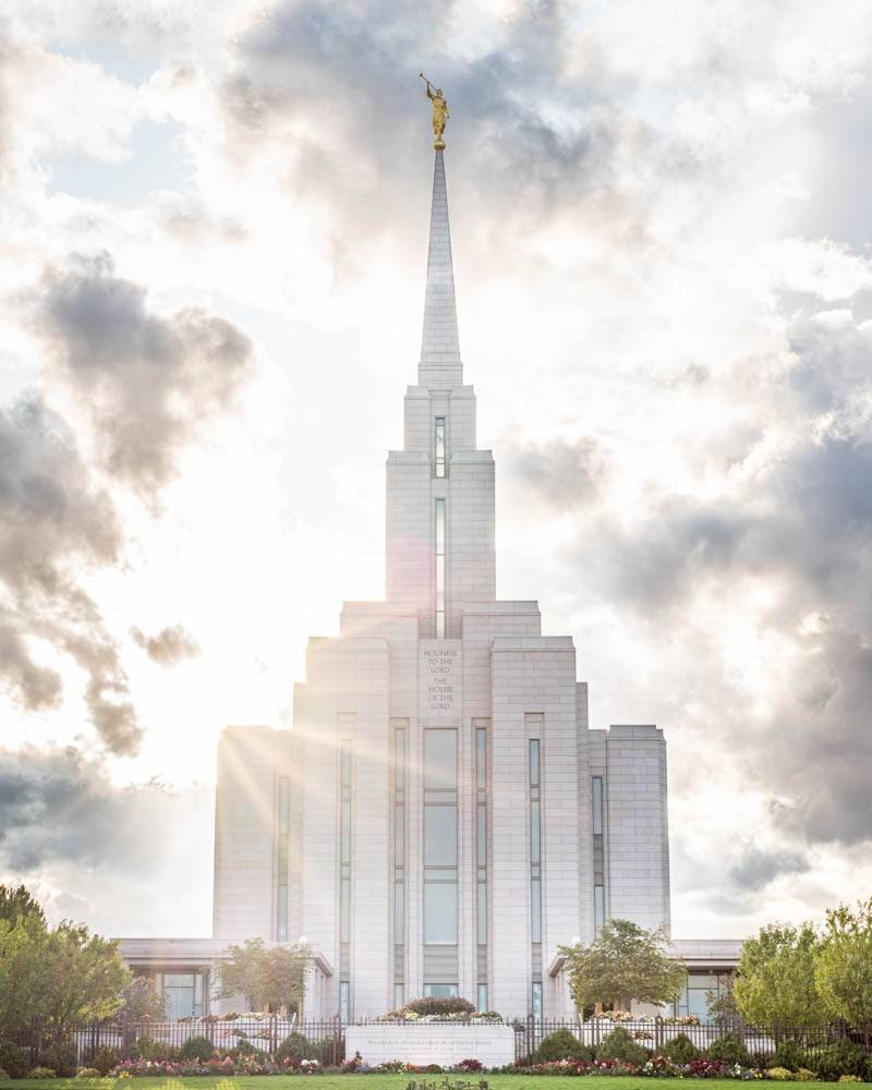 LDS art vertical photo of the Oquirrh Mountain Temple with sun beams shining out from behind.