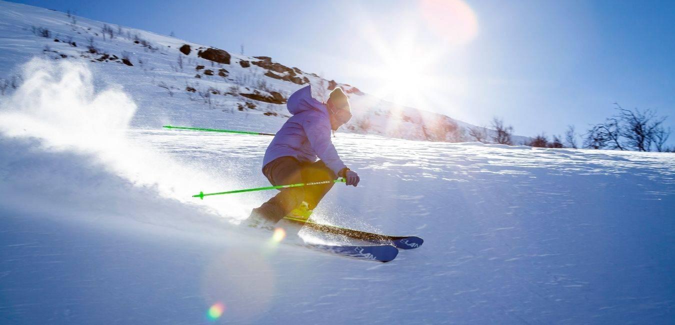 C'est une photo d'un skieur en hors-piste avec des skis de randonnée en train de faire un virage dans la neige sur le sommet d'une montagne.