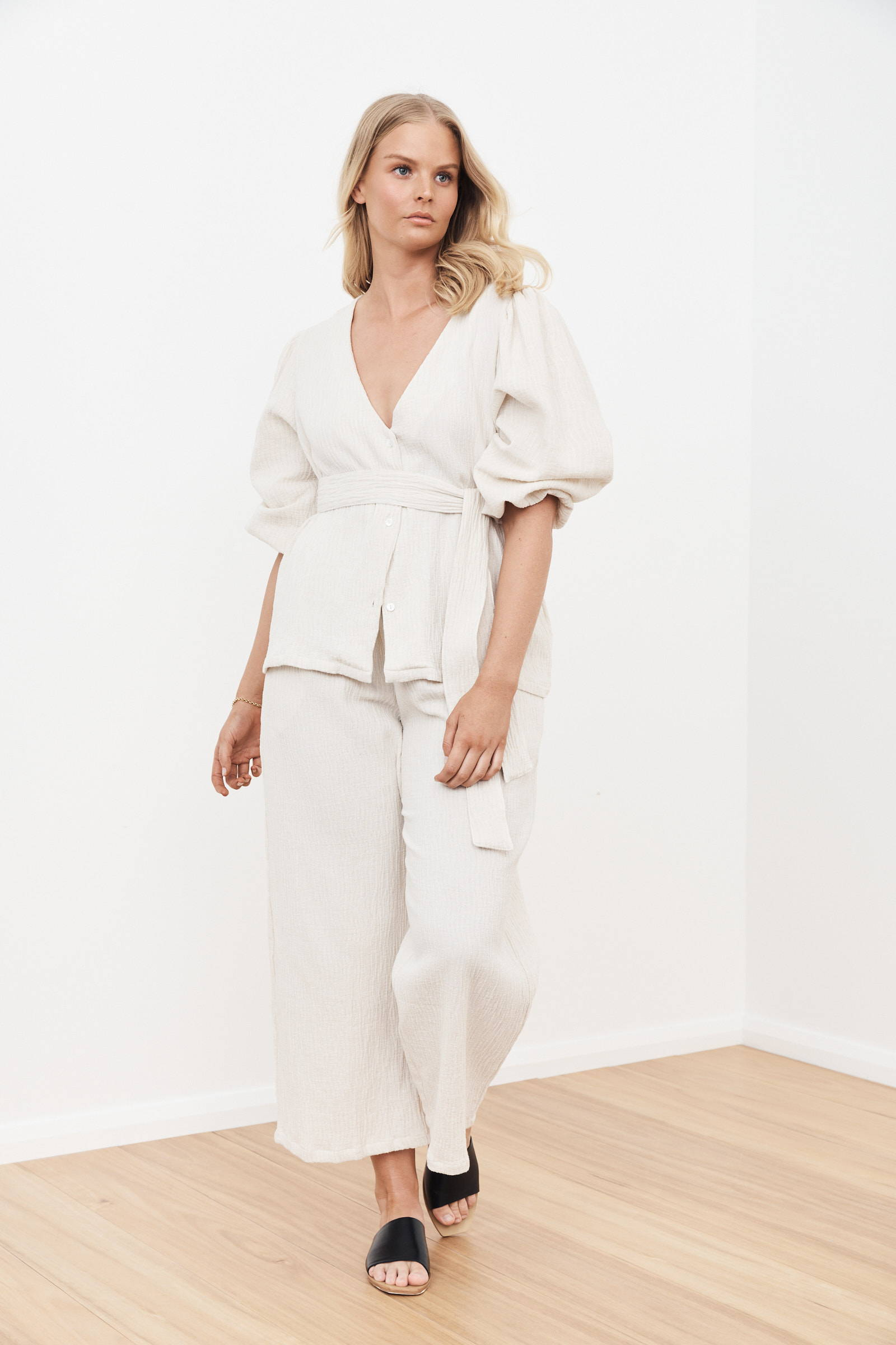 blonde woman wearing wide leg linen pants and puff sleeve top with waist sash