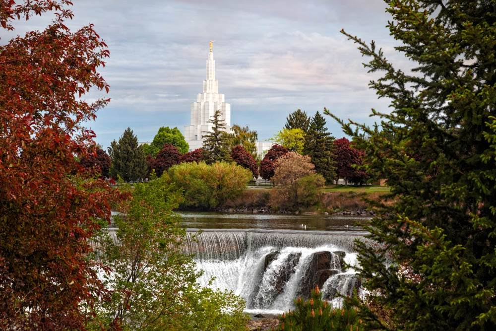 Idaho Falls Temple and water falls framed by autumn trees.